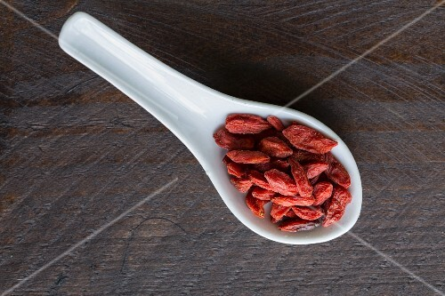 Goji berries on a porcelain spoon on a dark surface
