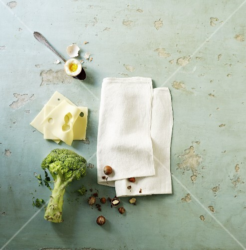 A soft-boiled egg, cheese, broccoli and a napkin on a stone surface