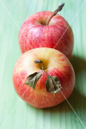 Two organic apples with stems and leaves
