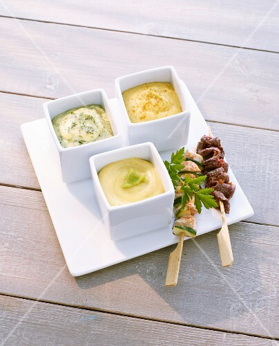 Herb mayonnaise, wasabi mayonnaise and curry mayonnaise as a dip for skewers