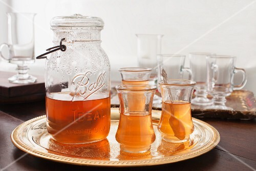 Tea in a glass jug with a handle and tea glasses on a golden tray
