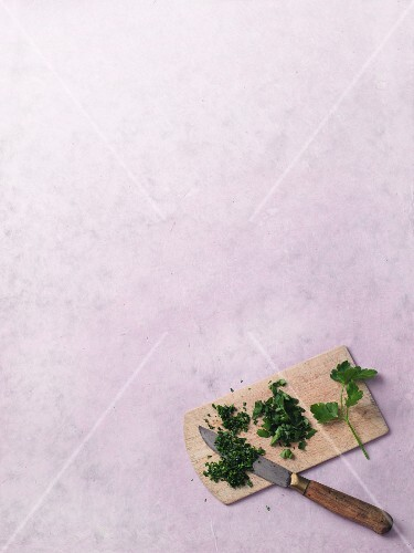 Chopped herbs on a chopping board with knife