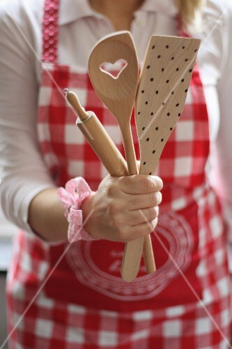 A woman wearing a red-and-white apron and a wooden spoon