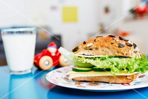 A cheese roll with cucumber and lettuce with a glass of milk and a toy car in the background