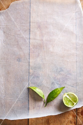 Half a lime with leaves on a piece of paper