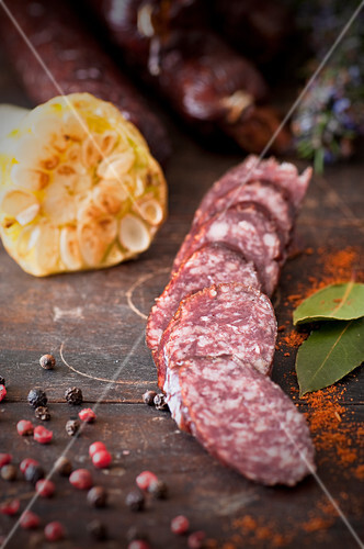 Sliced venison sausage with garlic and peppercorns on a wooden chopping board