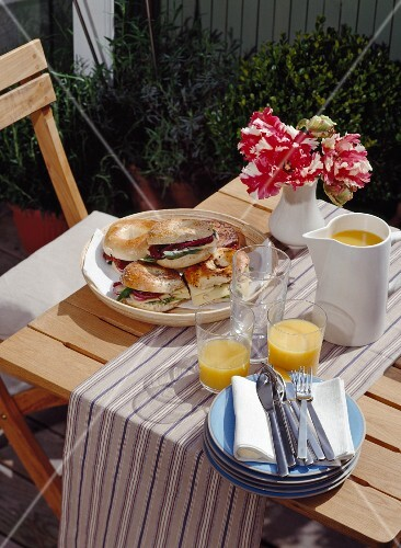 Breakfast table laid on the terrace of an inner-city apartment with bacon bagels and orange juice