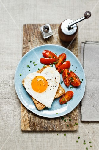 A slice of toast topped with a heart-shaped fried egg served with cherry tomatoes