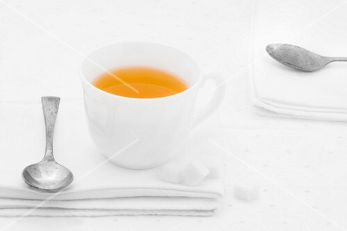 A cup of tea with sugar lumps and spoon on a white fabric napkin