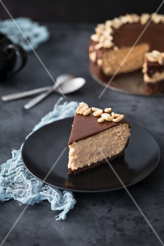 A slice of caramel cheesecake with chocolate and peanuts