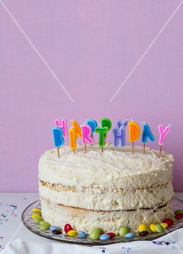 A child's birthday cake decorated with colourful letter candles
