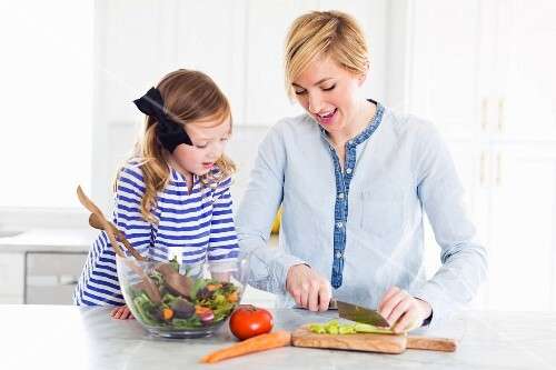 A mother and daughter preparing salad in a kitchen