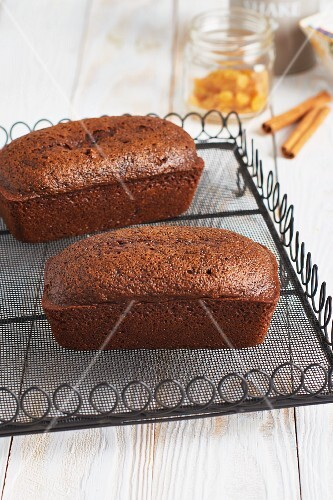 Two loaves of spiced cake on a delicate wire rack