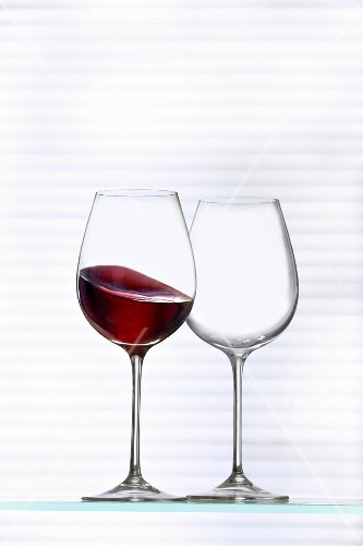 An empty wine glass and a glass of red wine