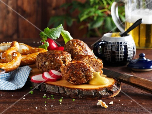 Meatballs with radishes, mustard and pretzels