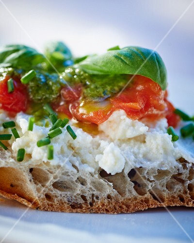 A slice of bread topped with goat's cheese, pesto and tomatoes
