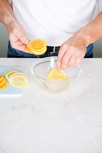 Citrus fruit slices being dipped into sugared water