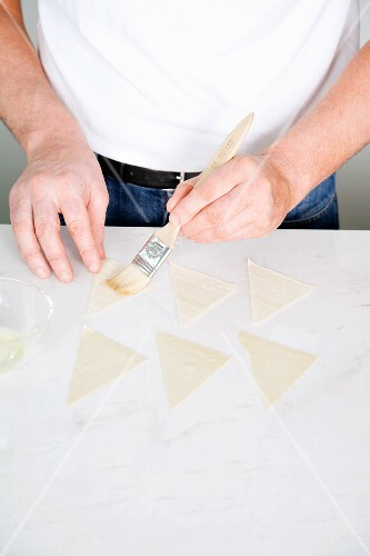 Wonton sheets being brushed with water