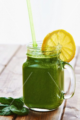 A green smoothie with a slice of lemon