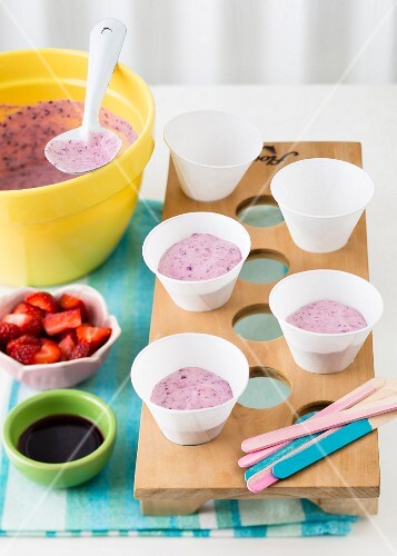 Berry yoghurt ice cream being transferred to cups