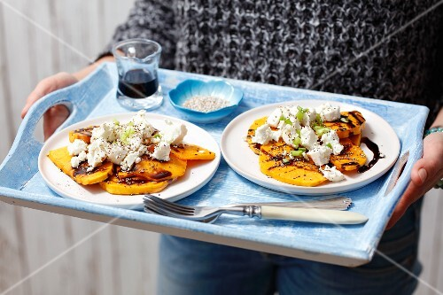 A woman holding plates of grilled pumpkin with goat's cheese on a tray