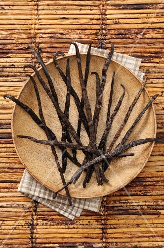 Vanilla pods on a wooden plate