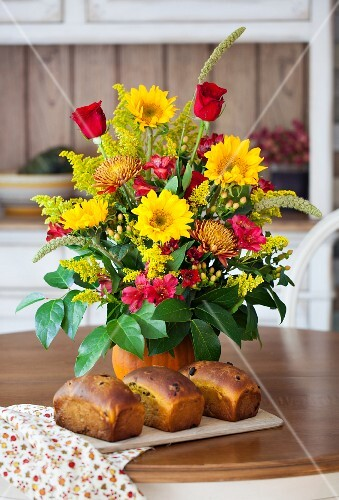 Three loaves of pumpkin bread with raisins, dried cherries and pumpkin seeds in front of a bouquet of flowers