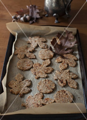 Autumnal leaf-shaped pumpkin seed and flaxseed crackers on a baking tray