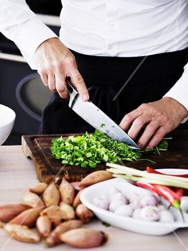 A man slicing coriander on a wooden board