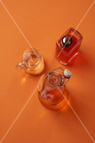 Three different types of vinegar in a carafe, a flip-top bottle and a dosing bottle