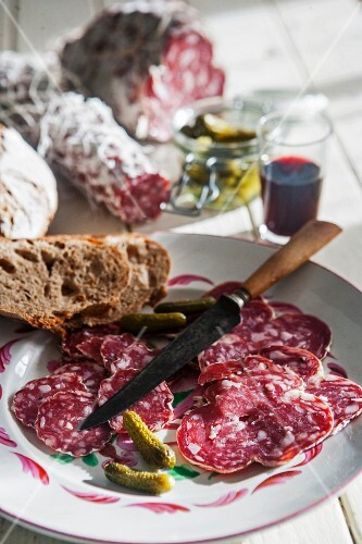 A salami platter with gherkins and bread
