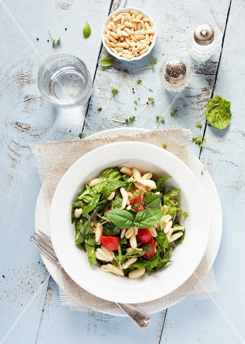 A bowl of pasta and spinach salad with tomatoes and pine nuts