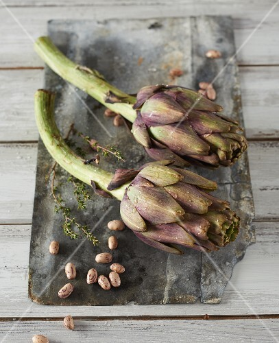 Artichokes, beans and thyme on a wooden board