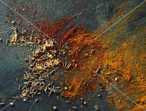 Ground paprkia, tumeric, cumin and fennel seeds on a slate platter
