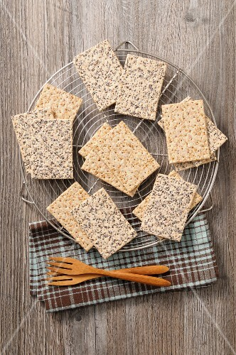 Crackers with sesame seeds and poppyseeds on a cooling rack (seen from above)