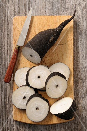 Black radish, partially sliced, on a chopping board