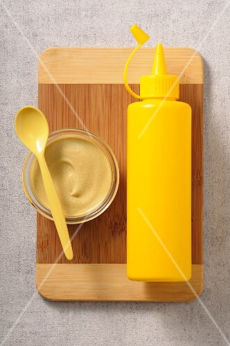 Mustard in a glass bowl next to a yellow plastic bottle