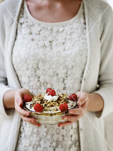 A woman holding a bowl of white chocolate mousse with honey, roasted nuts and fresh raspberries