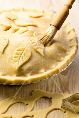 Apple pie being made: lid being decorated with pastry leaves