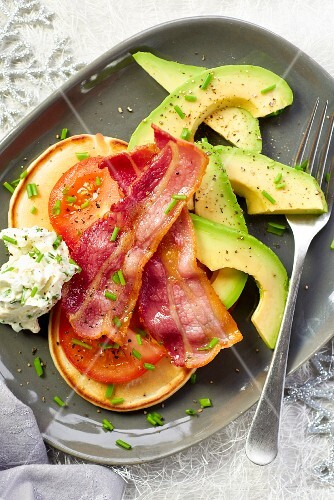 Pancakes with bacon, tomatoes and avocado