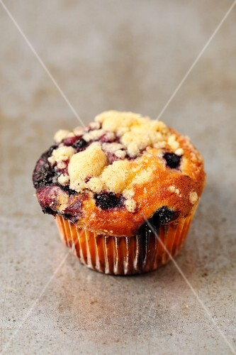 A yoghurt cupcake with blueberries and crumbles