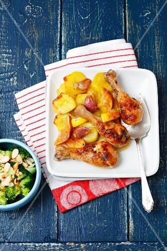 Baked chicken drumsticks with lemons and potatoes served with steamed broccoli and flaked almonds