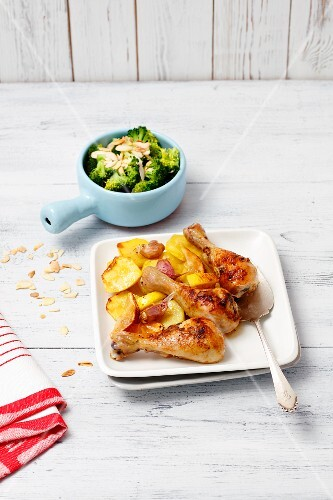 Chicken drumsticks with lemons and potatoes served with steamed broccoli and flaked almonds