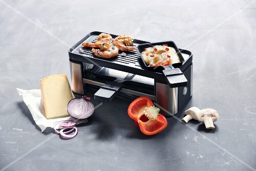 A raclette for two pans with a grill surface surrounded by ingredients for raclette