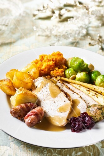 Christmas dinner with turkey, pigs in blankets, potatoes and Brussels sprouts