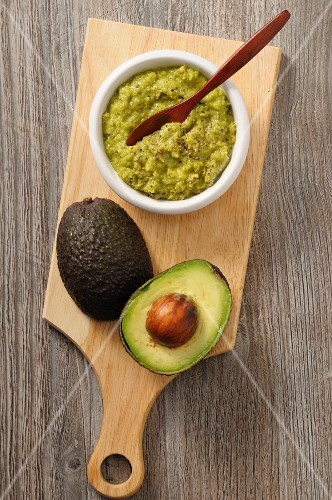 Guacamole and a fresh avocado on a chopping board