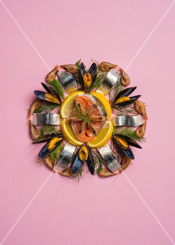 A decorative flower made from fish, mussels, lemons and dill