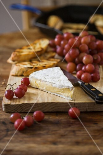 Brie, red grapes and grilled bread on a chopping board