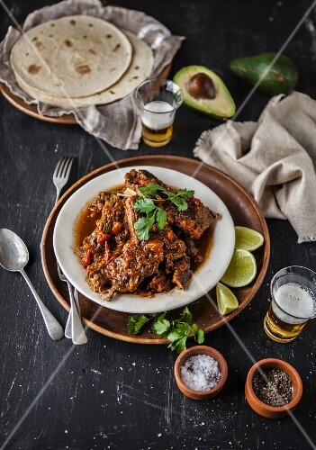 Braised beef ribs with spices, tortillas and beer