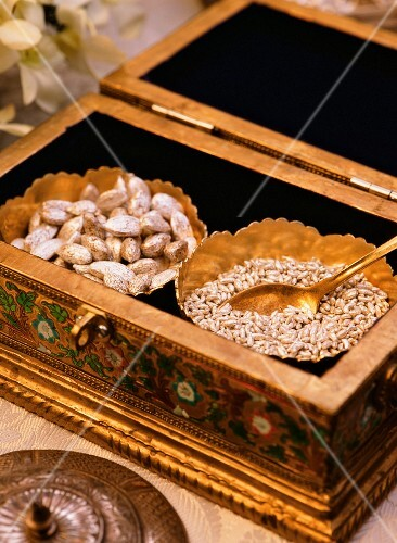 Cardamom pods and pine nuts in a gilded box